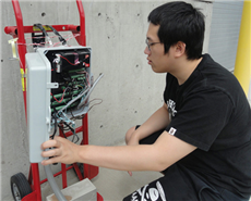 Chemical engineering student Ka Fung Wong looks at the data log that's gathering information from sensors buried under the concrete test plot.