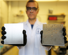 Dr Tarek Awad, a researcher in U of T's Department of Materials Science & Engineering, shows two samples: at left, a stainless steel surface treated to trap simple cooking oil, and at right, an uncoat